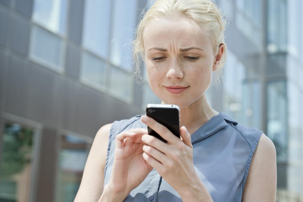 Jeune femme qui essaye ses verres de lunettes Essilor en ligne sur son smartphone.