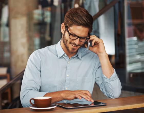 Homme au téléphone devant une tablette portant des lunettes avec des verres Essilor munis de la technologie Eye Protect System